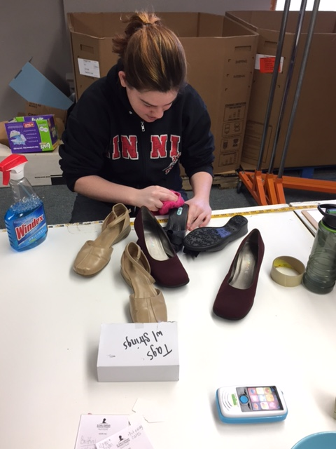 CBVI Student working to clean shoes for thrift store
